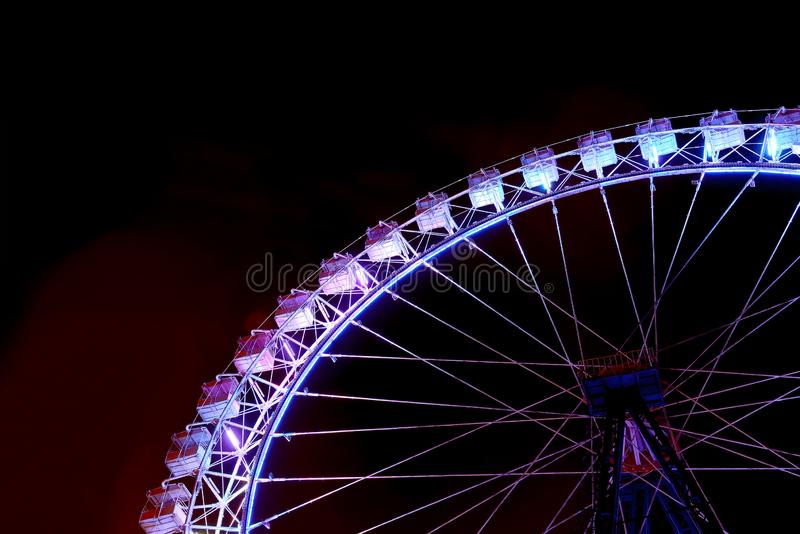 Part of ferris wheel with purple lighting at night royalty free stock image