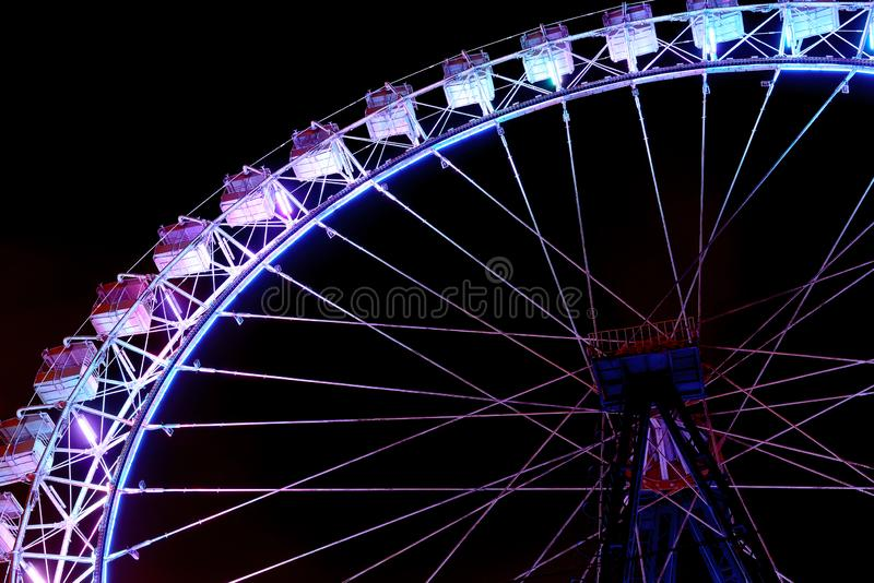 Part of ferris wheel with purple lighting at night royalty free stock photo
