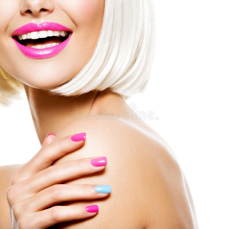 Part of a fun female face  with multicolor nails and white hairs. Studio photo stock photo