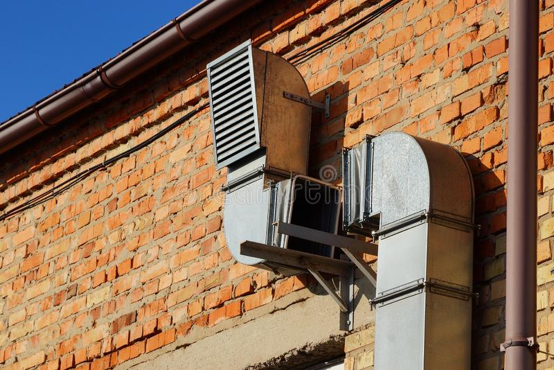 Part of a gray long metal hood on a brown brick wall royalty free stock photo