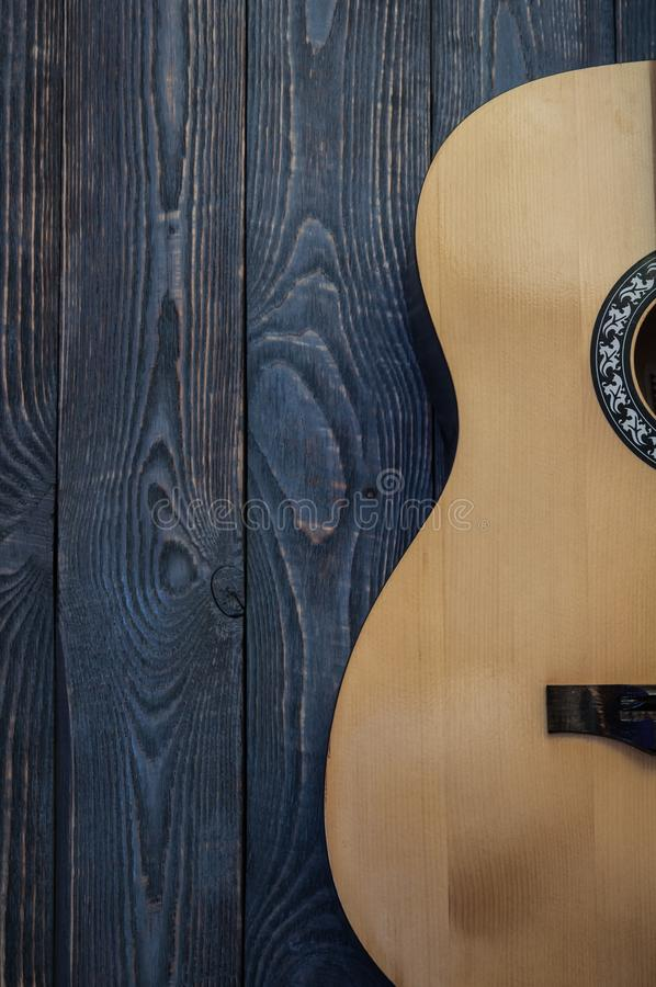 Part of the guitar standing on a wooden textured wall vertically. Side view stock image