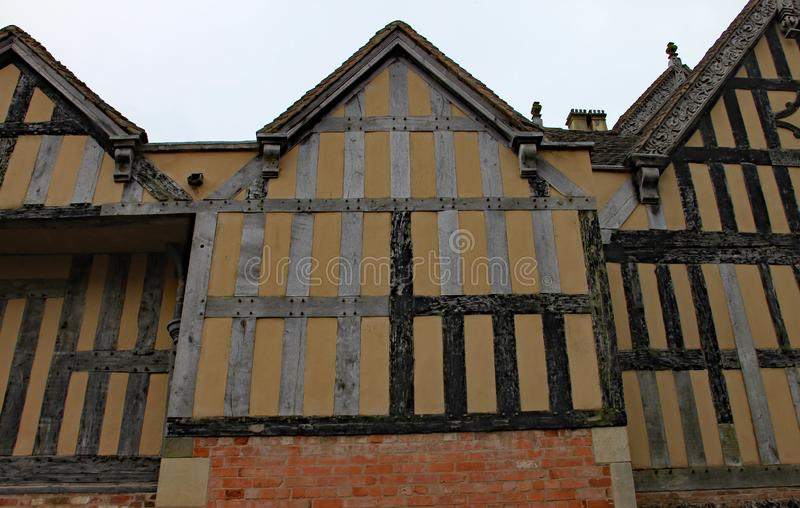 Part of a half timber framed building with ornate carvings on some of the facia boards royalty free stock photography