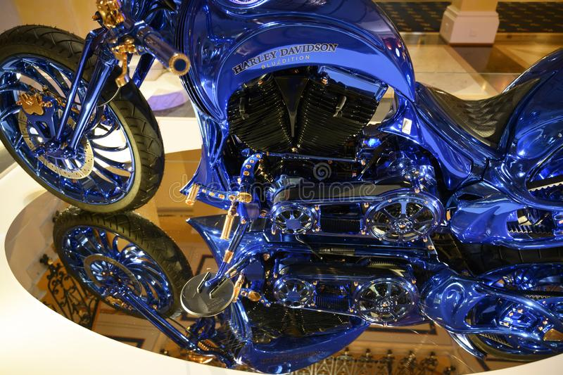 Part of Harley Davidson Blue Edition with front wheel, zylinder blocks, tank, seat blue and gold standing on mirror stock photography