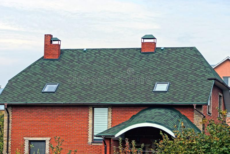 Part of the house with a green tiled roof and a red brick wall with windows. Against the sky stock image