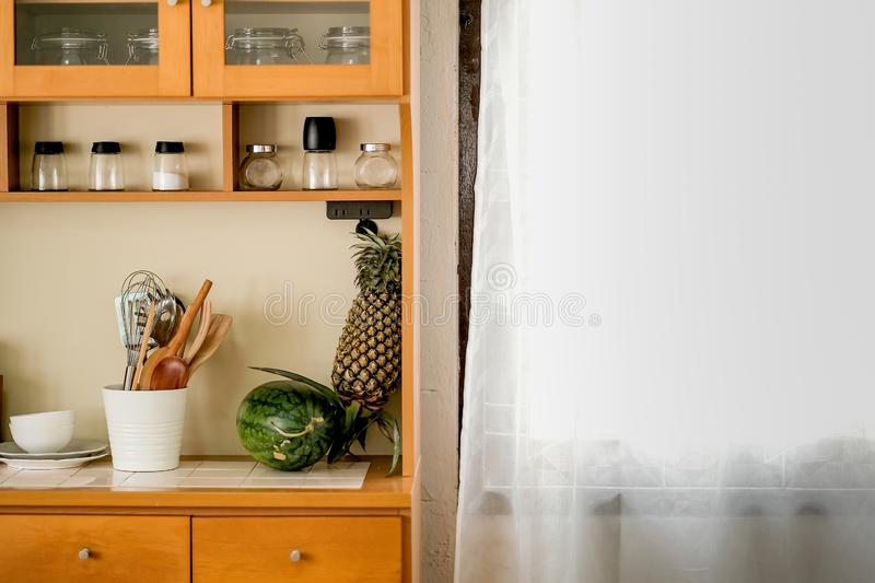 Part of kitchen area contain some accessories and fruit include water melon and pineapple in house near the window with white. Curtain during day time royalty free stock photos