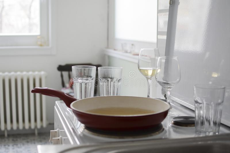 Part of the kitchen and dishes after intimate lunch or dinner for two with white wine. royalty free stock image