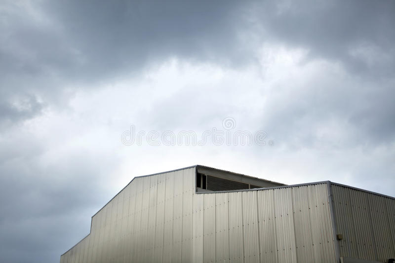 Inclement Hangar. Part of a large hangar/warehouse with squigguly metal walls, under storm clouds overcast gray skies on an inclement winter day stock images