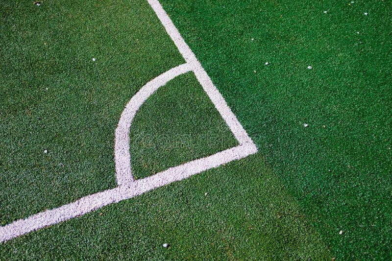 Part of the layout of the football field, the position of the corner kick. White marking lines on the green grass of the sports stock images