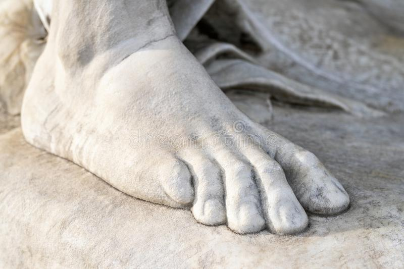 Part of leg of ancient marble statue. Close-up stone foot. Pedicure and feet care concept.  royalty free stock photos