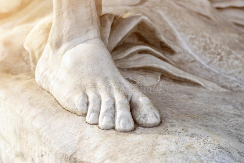 Part of leg of ancient marble statue. Close-up stone foot. Pedicure and feet care concept.  stock photos