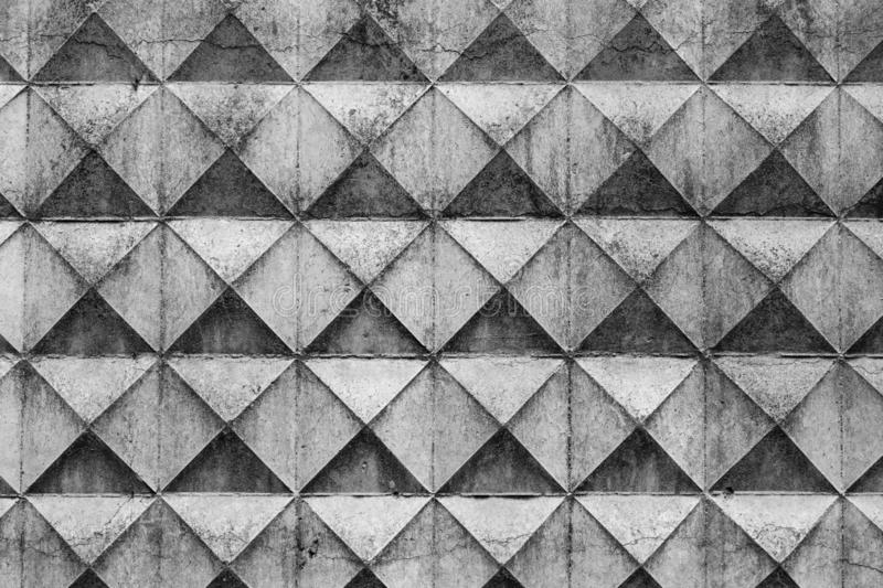 Part of a light concrete fence with rhombuses. White relief concrete wall with geometric shapes stock photo