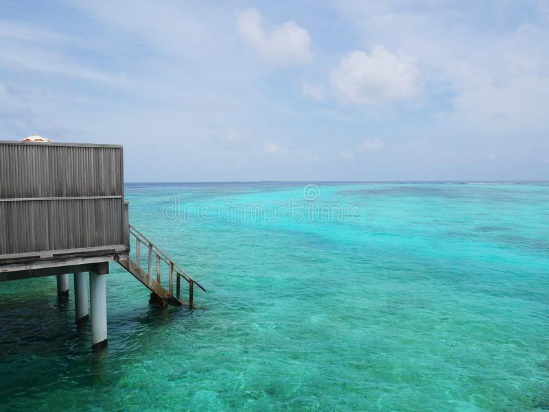 Part of Maldives water villa room in an island resort, seeing wood stairs down from balcony to ocean floor. royalty free stock photos