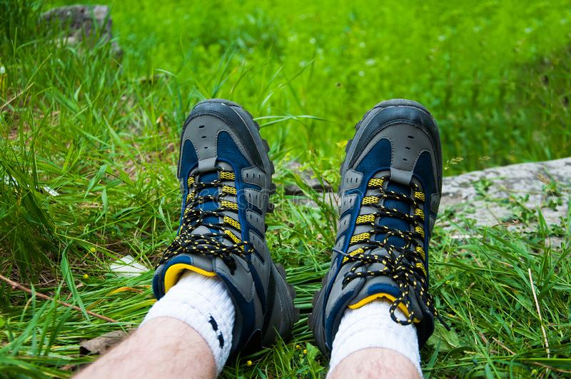 Part of man`s legs. In blue trekking boots. On the green grass stock photo