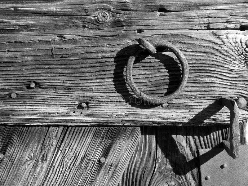 Part of a medieval barn door with wood grain and iron rings in black and white. Wooden boards of an old gate with visible wood grain in black and white, Iron stock images