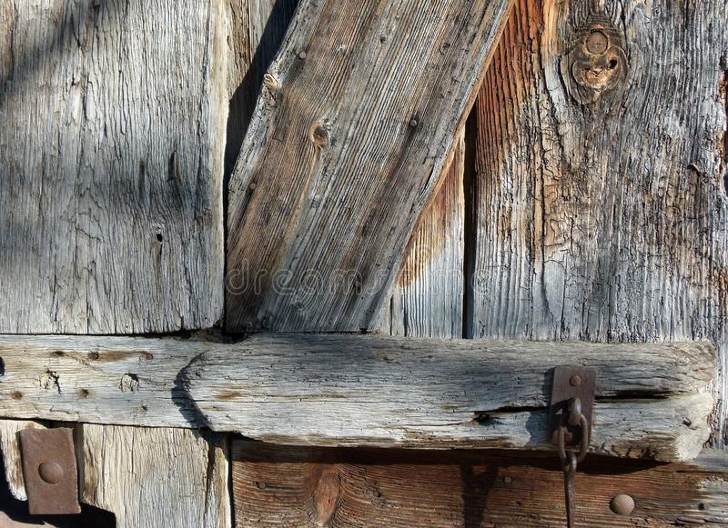 Part of a medieval barn door with wood grain and iron rings 2. Wooden boards of an old gate with visible wood grain, Iron fittings in a very old wooden gate royalty free stock photo