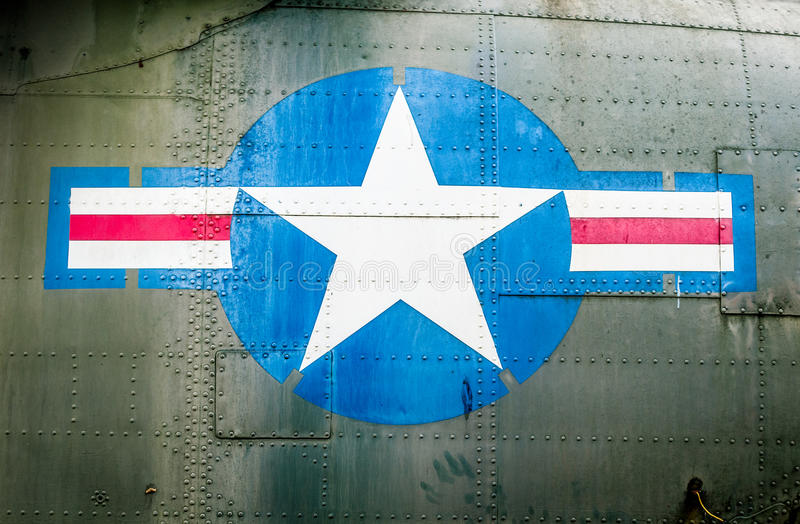 Military plane with star and stripe sign. Part of military airplane with United States Air Force sign. Big white star in blue circle with stripes aside. War stock photo