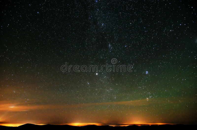 Part of Milky way over city lights and mountains stock photo