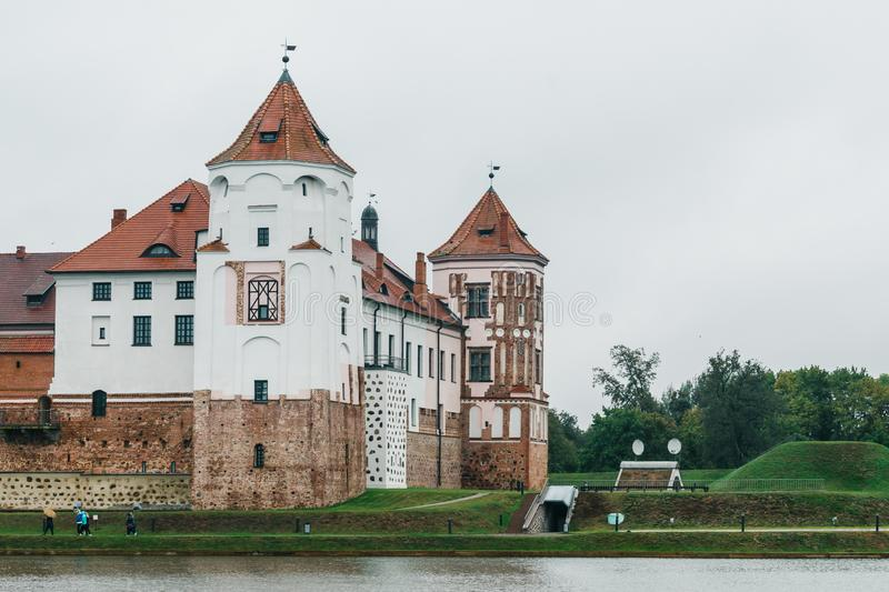 Part of the Mir Castle complex on the lake in cloudy weather. Watchtowers stock photography