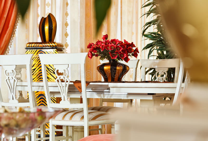 Part of modern art deco style dining room interior. Part of modern art deco styledining room interior with golden striped vase and red flowers stock photography