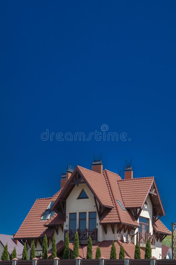 Part of a modern brick house under a tiled roof on a sky background. Cottage with balcony. Two-storey house. Wooden house. Living. In nature. Finishing natural stock images
