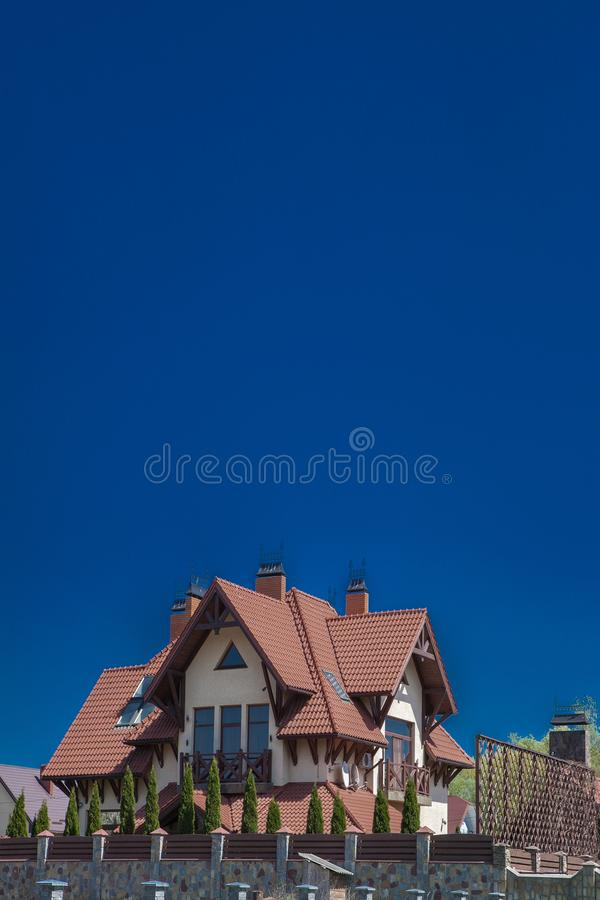 Part of a modern brick house under a tiled roof on a sky background. Cottage with balcony. Two-storey house. Wooden house. Living royalty free stock photos