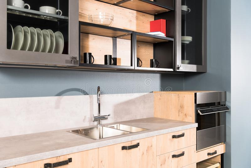 part of modern clean light kitchen with sink tap and shelves royalty free stock photos