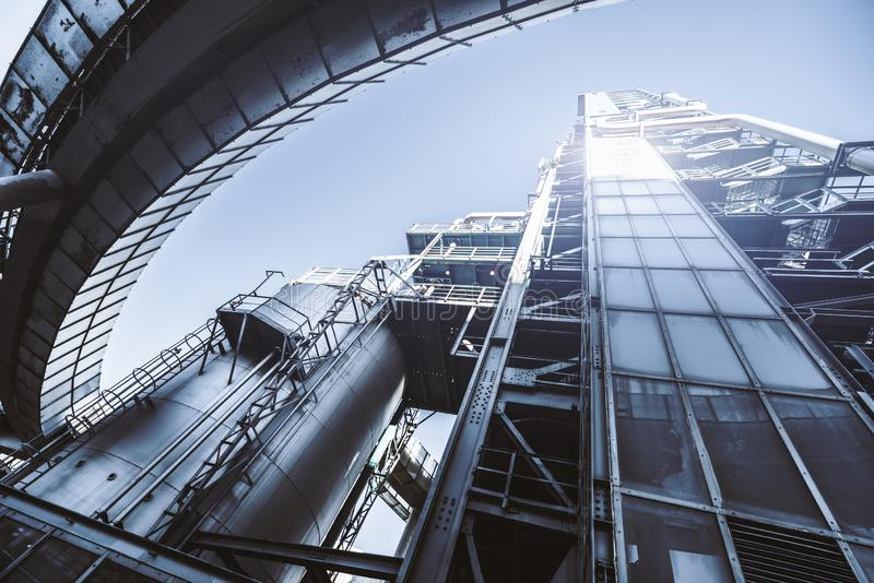 Part of a modern oil refinery. A wide-angle view from below of a contemporary fuel plant factory facility building with multiple metal tubes, elevator, stairs stock images