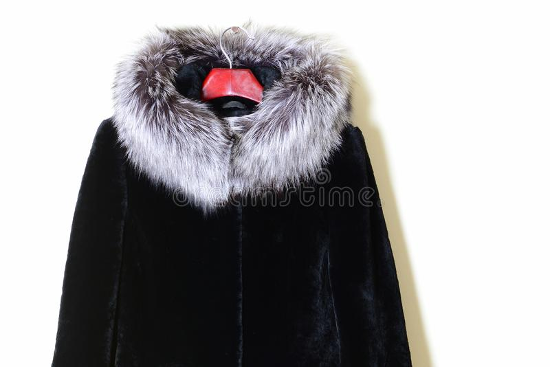 Part of a natural fur coat-mouton with a fur collar made of silver fox, close-up. Winter outerwear on a hanger. Collection 2017-2018 stock photos
