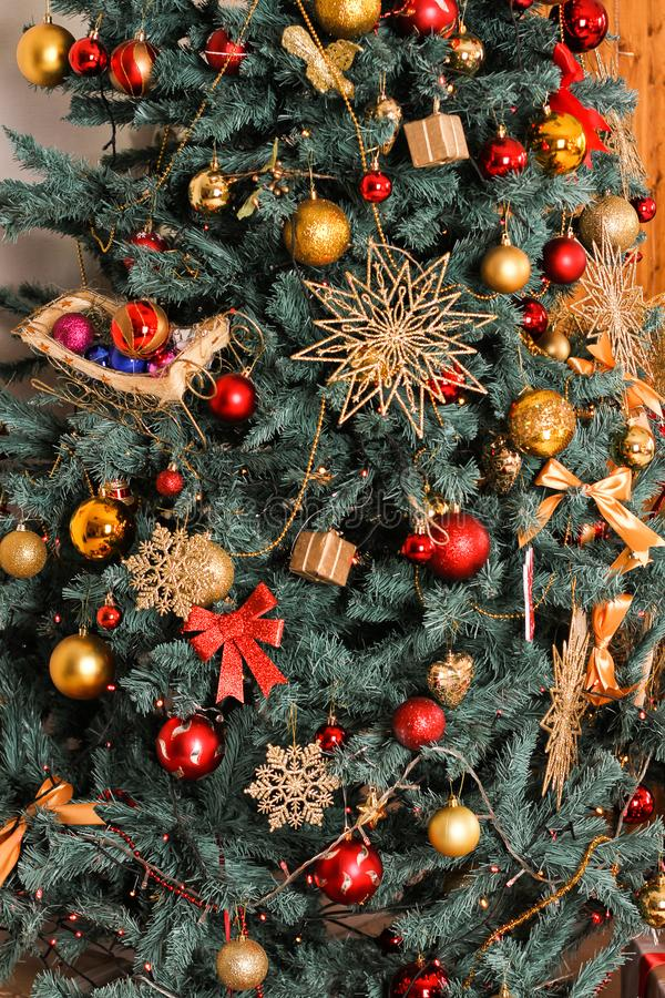 Part of the New Year green tree decorated with red toys, spheres, a star, gifts, snowflakes and gold thread of a garland royalty free stock photos