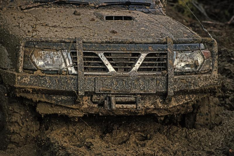 Part of offroad car stuck in mud on dark background. Part of offroad car stuck in deep mud on dark background. Bonnet, lights and bumper covered with dirt stock photo