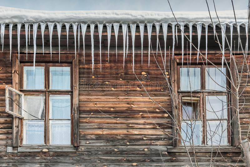 A part of an old brown wooden house with two old windows with wooden brown frames and a group of sharp bright white transparent. Icicles and snow and ice and stock photography