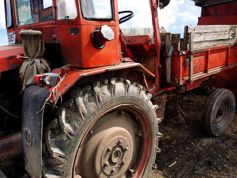 Old neglected dark red tractor with rubber dirty wheels stock photography