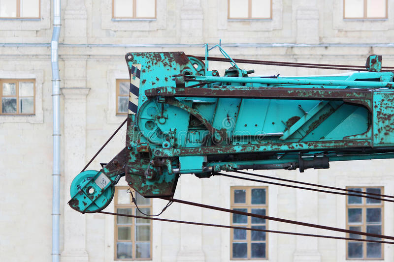 part of old working turquoise crane truck for construction on a background Palace. royalty free stock image
