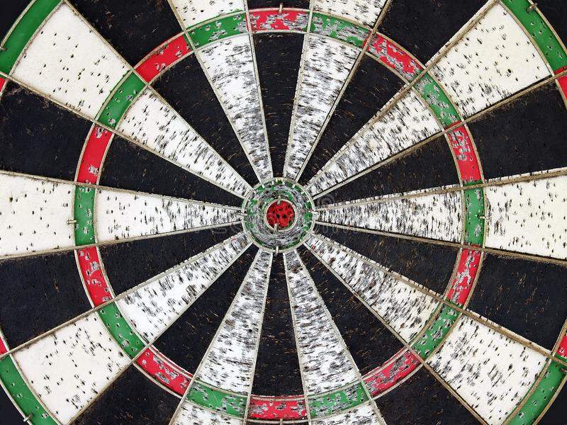 Close up part of oldish colorful wooden dart board with red color bulls eye target and porous caused by hard training royalty free stock images