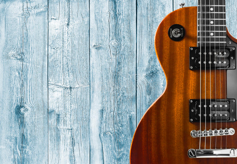 Part of the orange electric guitar on wooden background. A place for writing of the text. Part of the orange electric guitar on wooden background. A place for royalty free stock photos