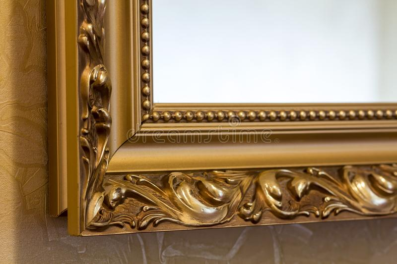 Part of the ornate, golden color carved mirror frame in ancient. Style royalty free stock photo