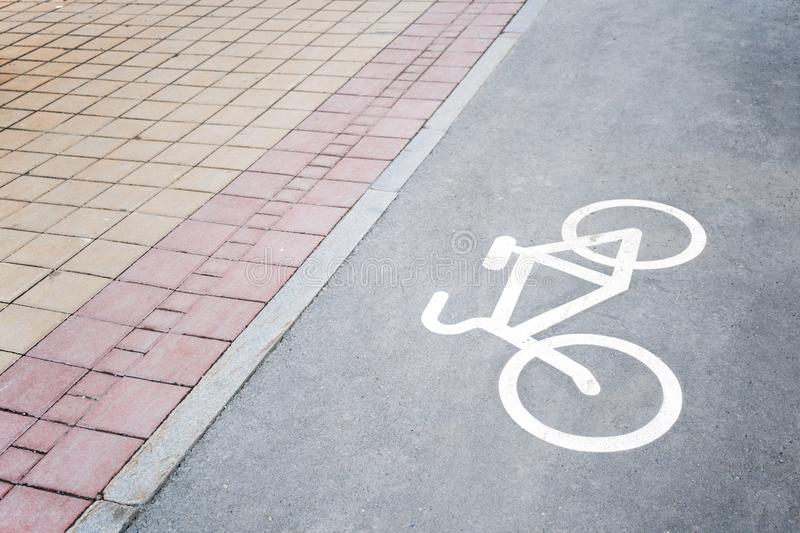 Part of paved sidewalk and bike paths with the image of bicycle. Close-up part of paved sidewalk and bike paths with the image of bicycle. Top diagonal view royalty free stock image