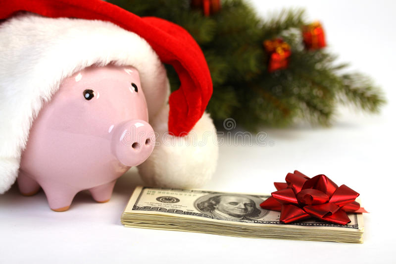 Part of piggy bank with Santa Claus hat and stack of money american hundred dollar bills with red bow and christmas tree standing stock image
