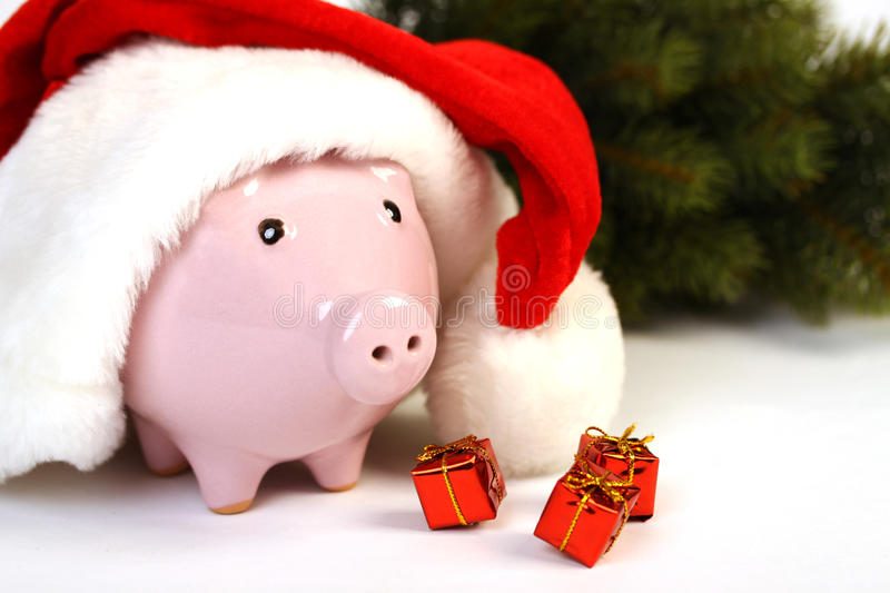 Part of piggy bank with Santa Claus hat and three little gifts and christmas tree standing on white background stock photography