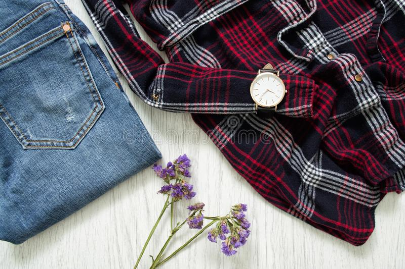 Part of plaid shirts, watches, jeans and wildflowers. Fashionable concept.  royalty free stock photo