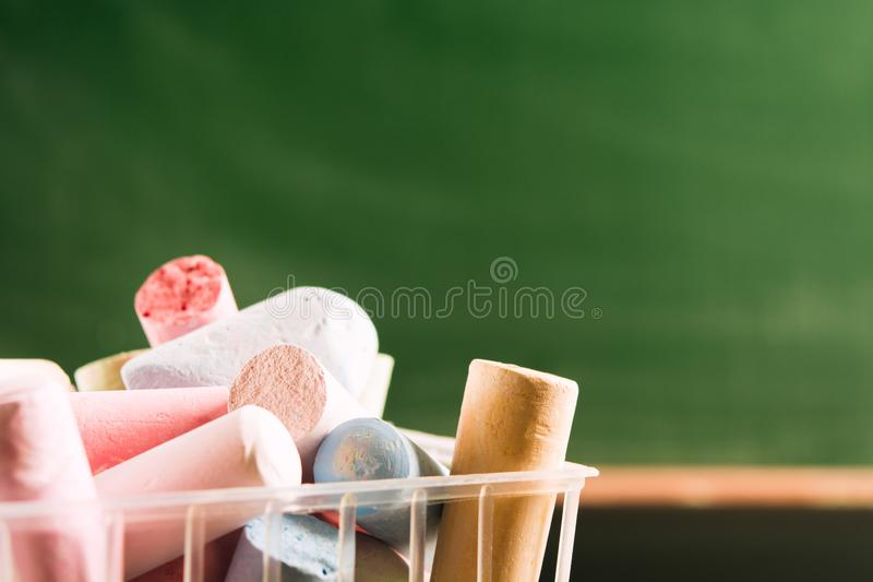 Part of plastic basket with many colorful piece of chalk. Back to school concept. Beginning school year. Closeup view with copy. Space. Selective focus royalty free stock photos
