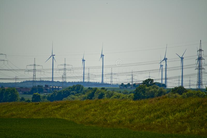 Part of a power line with wind turbines in Bavaria, Germany stock photo