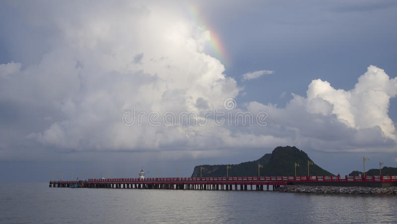 A part of Rainbow with blue sky and cloud over Red long bridge and the sea, mountain in background, peace wave stock photo