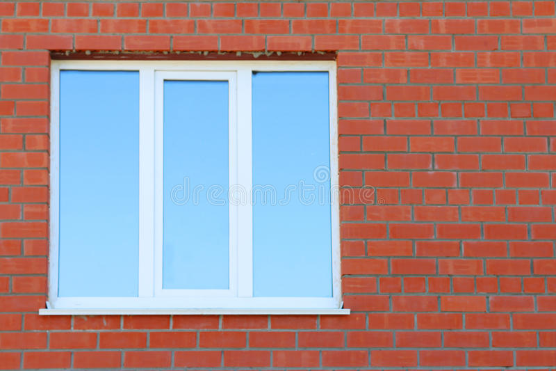 Part of red brick wall and blue window with double glazing. Of building stock photo