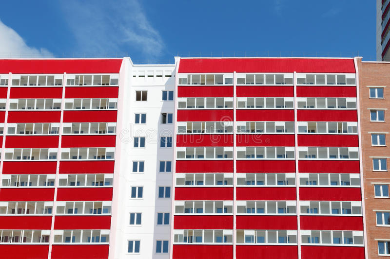 Part of residential building with many red loggias at sunny stock photo