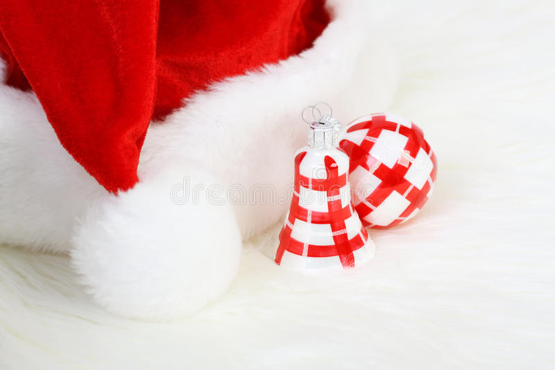 Part of Santa Claus hat with pom-pom and red and white Christmas ball and Christmas smaller bell on white fur stock photography