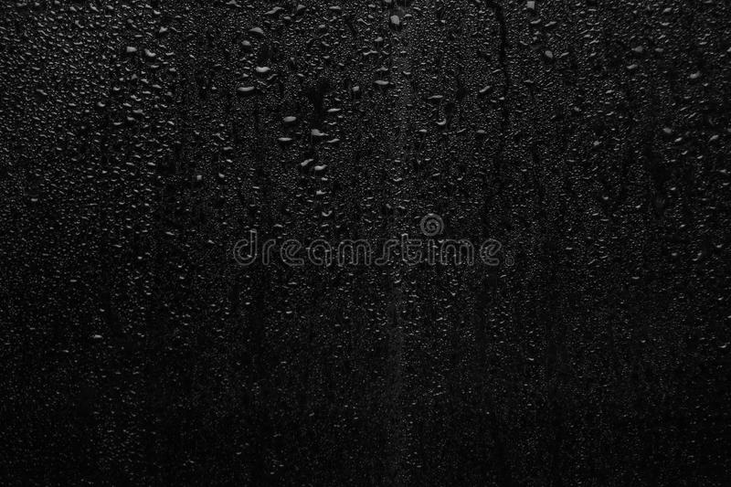 Part of series. Background photo of rain drops on dark glass, different size: small medium and large stock image