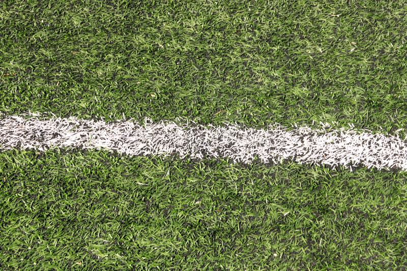 Part of sport soccer stadium and artificial turf football field. Detail, close up of green grass with white lines, goal line. stock images