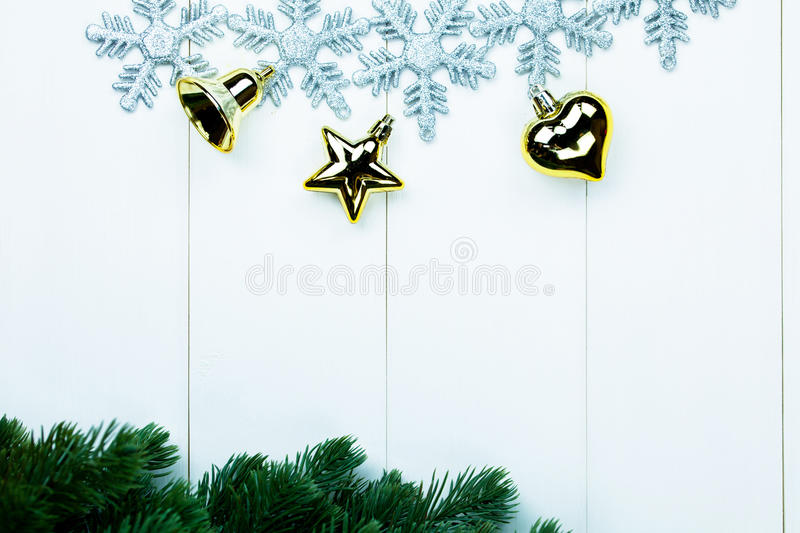 Part of spruce Christmas tree and golden ornaments and snowflakes on white wood background royalty free stock photos