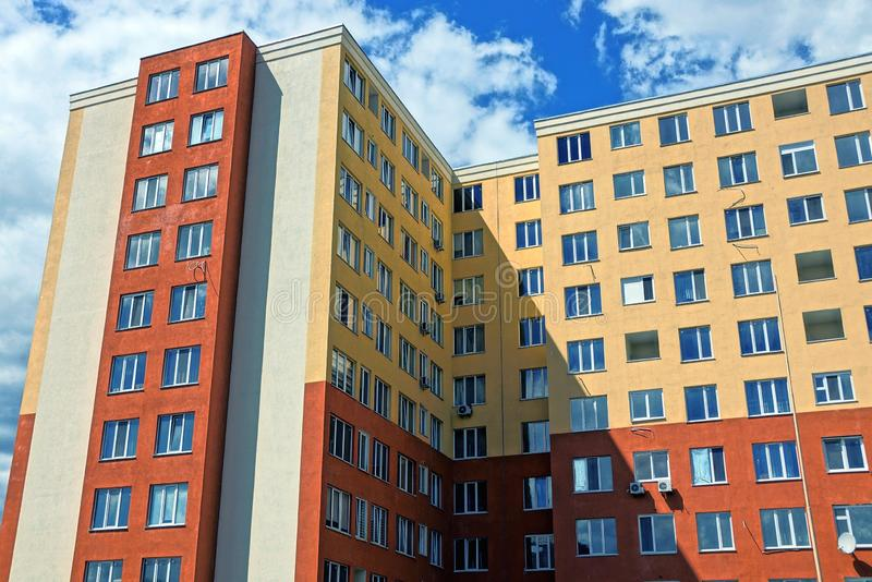 Part of a tall brown high-rise building with windows against the sky. And clouds stock photography